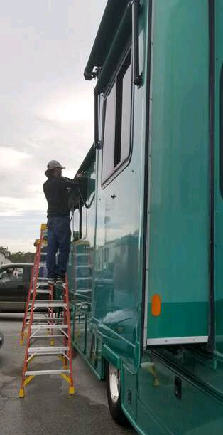 RV Awnings' worker replaces an awning fabric next to an aqua RV. Text below the picture says