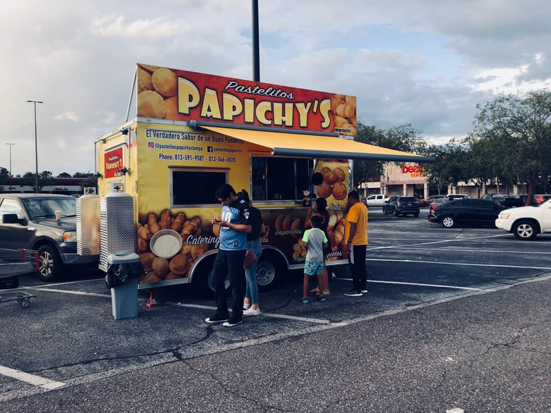 "A food truck ""Papichy's"" in a parking lot surronded by people under an awning shading them"