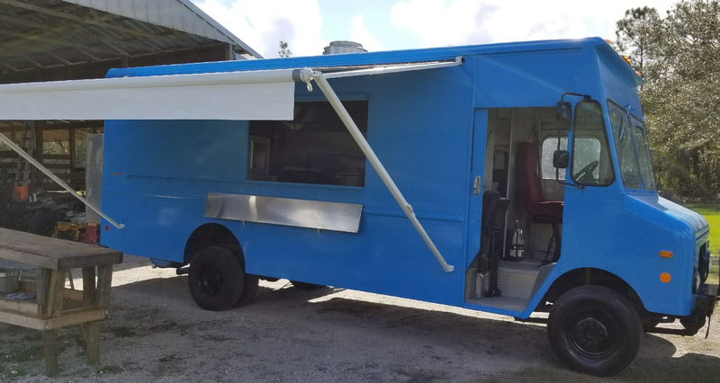 A blue food truck with an extended custom awning