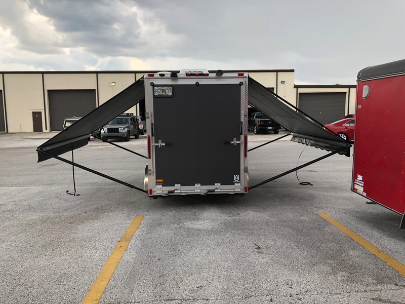A warehouse parking lot with a trailer and two custom awnings extended
