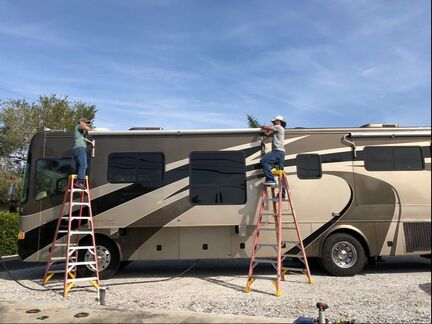 David Jones (Left) and John (right) perform an awning replacement on a RV underneath blue sky