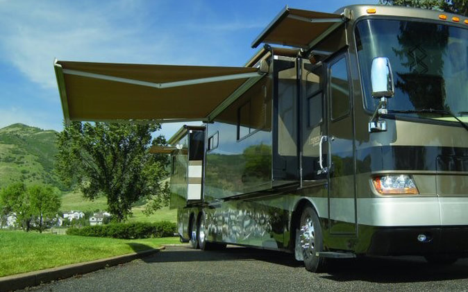 A RV with a patio and window awning extended