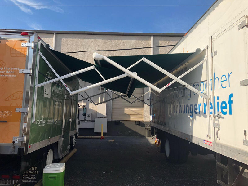 A food truck and a semi truck trailer with two extended custom awnings