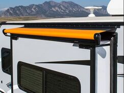 A RV with an orange alpine slideout cover