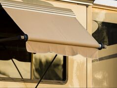 A tan window awning on an RV