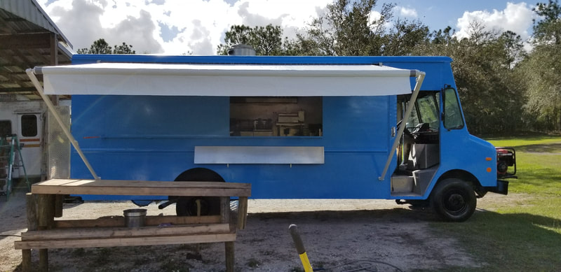 A blue food truck with an extended custom awning and picnic bench in front
