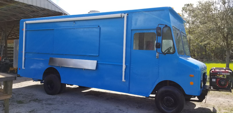 A blue food truck with a custom awning