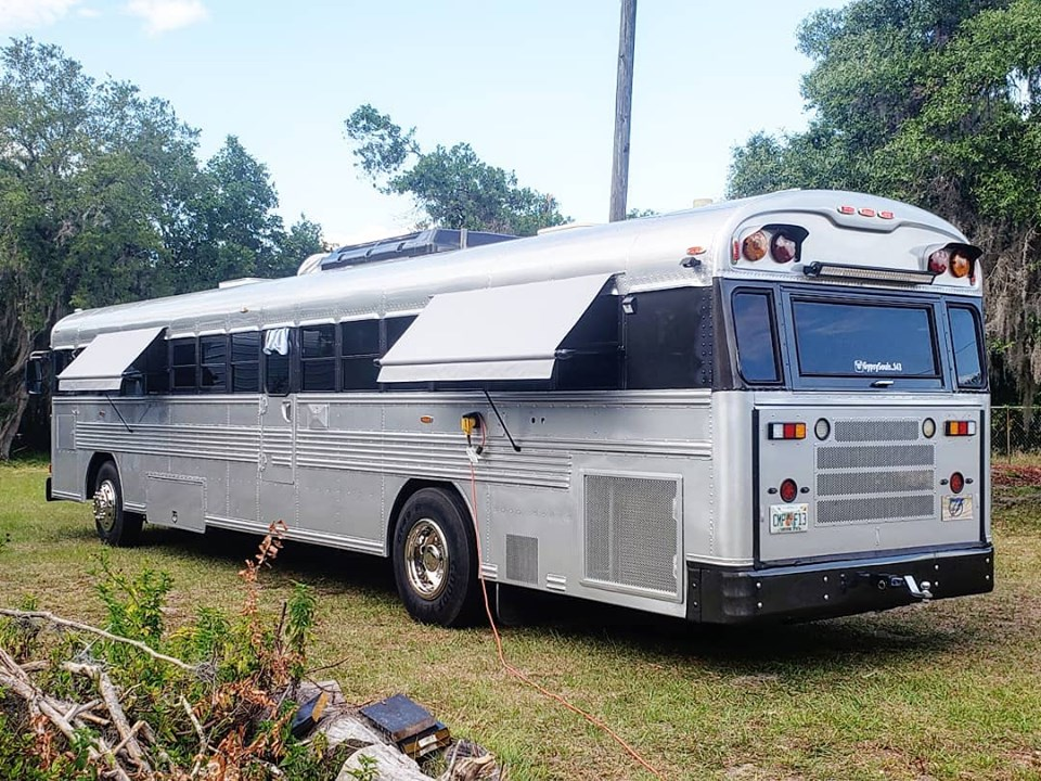 A silver bus with a custom awning