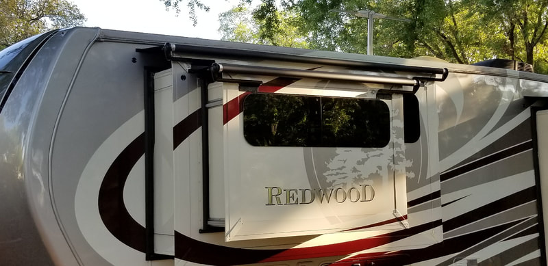 "A red and tan RV with ""Redwood"" on the side and a custom awning"